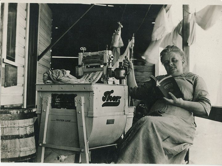 Woman reading next to one of the first washing machines